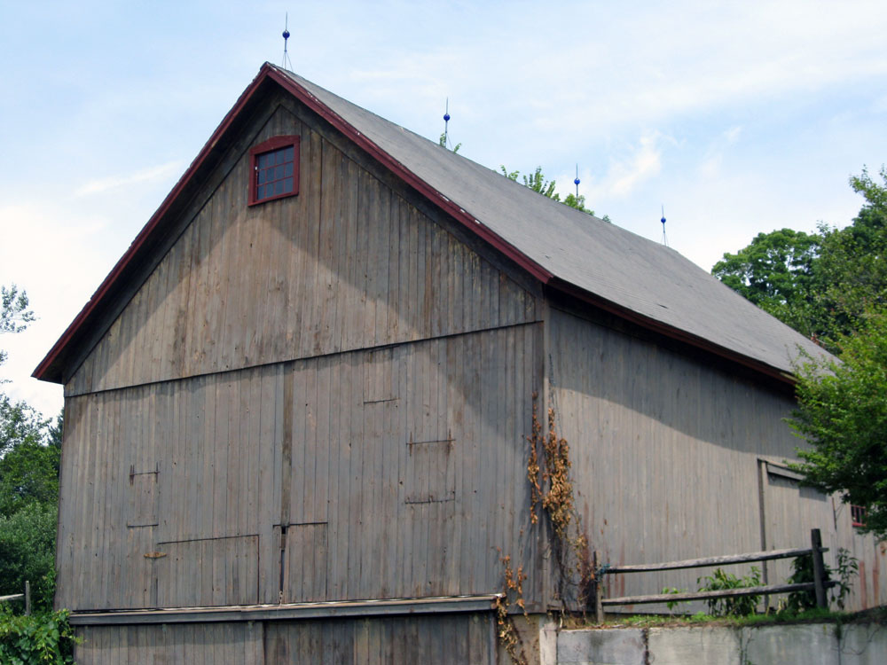 Antique Style Lightning Rods With Decorative Cobalt Blue Glass Ball  Ornaments And Tripod Supports On A Historical Barn.